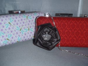 Two ab-fab hard-sided clutches, with a delicate silver chain as a strap.