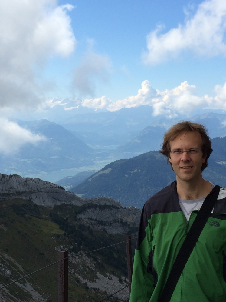 Mark on the front side of the mountain with snow-capped Alps in the background.