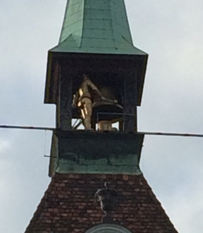 The bronze man at the top striking the bell with his hammer.
